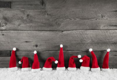 Weihnachtlicher Hintergrund Holz grau mit Weihnachtsmützen rot